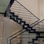 scala in acciaio nero verniciato e vetro, totem in acciaio inox effetto bugnato, detail cosciali pantografati